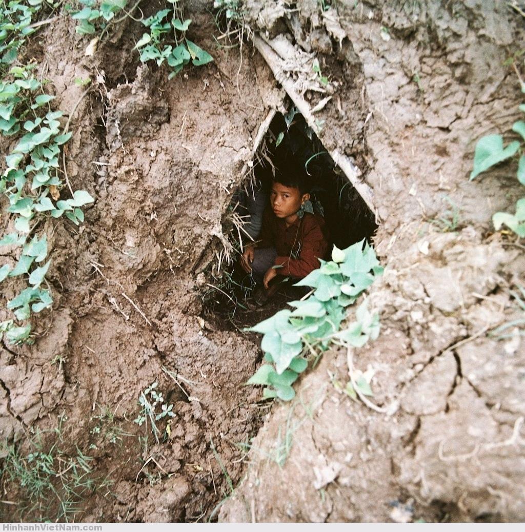 Em-bé-ngồi-trong-hầm-tránh-bom.