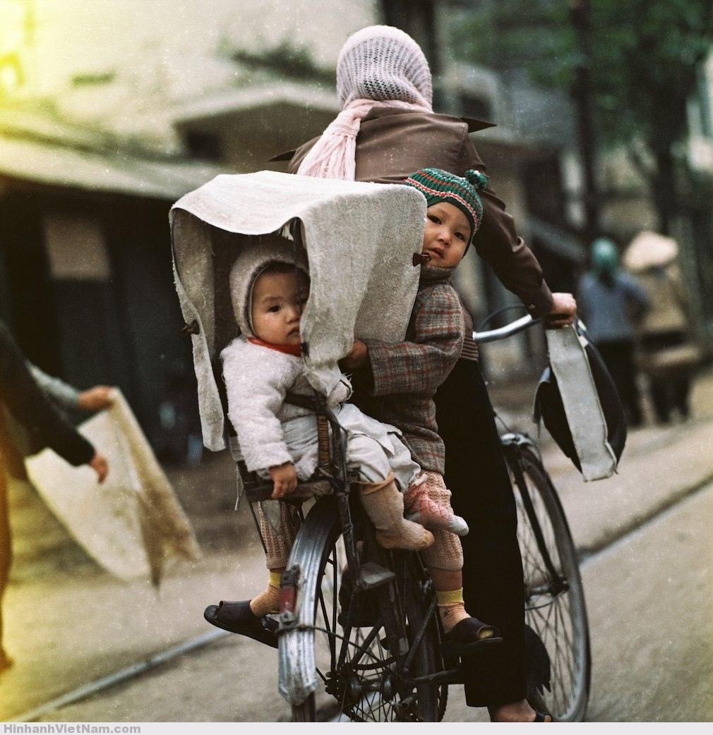 Hai-em-bé-được-mẹ-chở-bằng-xe-đạp-trên-phố